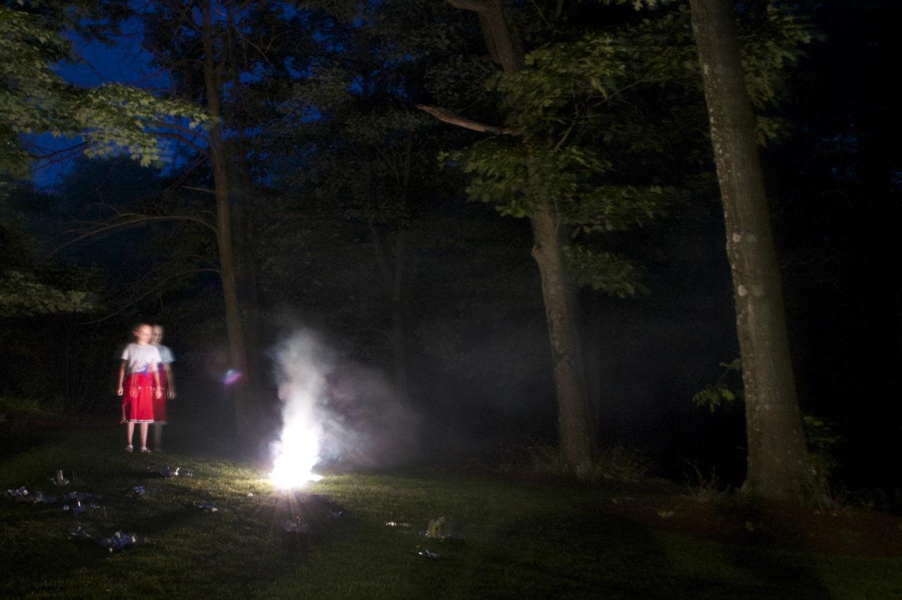 A child looks on at a blinding light in a dark forest.